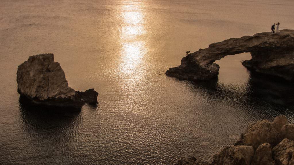Romantyczny zachód słońca na skalistej plaży Cypru