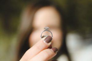 dziewczyna trzymająca na w palcach pierścionek zaręczynowy